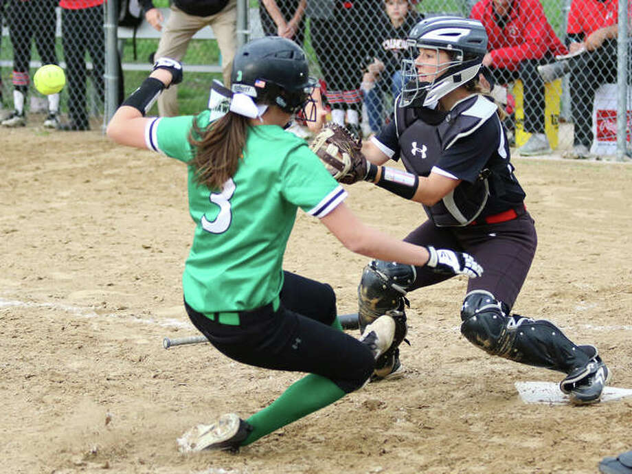 Carrollton's Marley Mullink (left) beats the throw to Calhoun catcher Mackenzie Cranmer on a squeeze bunt to score the tying run in the seventh inning Thursday at Wright Park in Carrollton. Calhoun won 5-4 in nine innings. Photo: Greg Shashack / The Telegraph