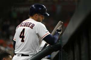 Houston Astros designated hitter George Springer (4) looks at his bat in the dugout during the seventh inning of an MLB baseball game at Minute Maid Park, in Houston, Thursday, April 25, 2019.