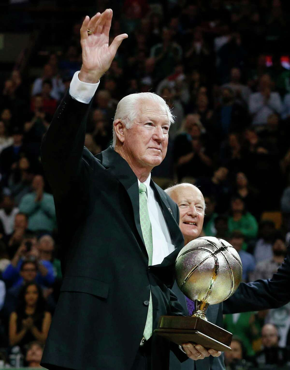 FILE - In this Tuesday, April 14, 2015 file photo, former Boston Celtics great John Havlicek waves while being honored on the court after the first quarter of an NBA basketball game against the Toronto Raptors in Boston. The Boston Celtics say Hall of Famer John Havlicek, whose steal of Hal Green?s inbounds pass in the final seconds of the 1965 Eastern Conference finals against the Philadelphia 76ers remains one of the most famous plays in NBA history, has died. The team says Havlicek died Thursday, April 25, 2019 at age 79. (AP Photo/Michael Dwyer, File)