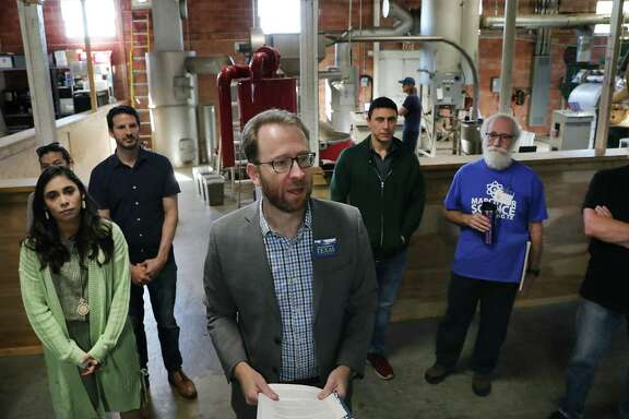 Luke Metzger, center, executive director of Environment Texas, leads a group of small business owners gathered at What's Brewing Coffee Roasters, to call on the City Council to adopt the proposed Climate Action and Adaptation Plan on April 25, 2019.