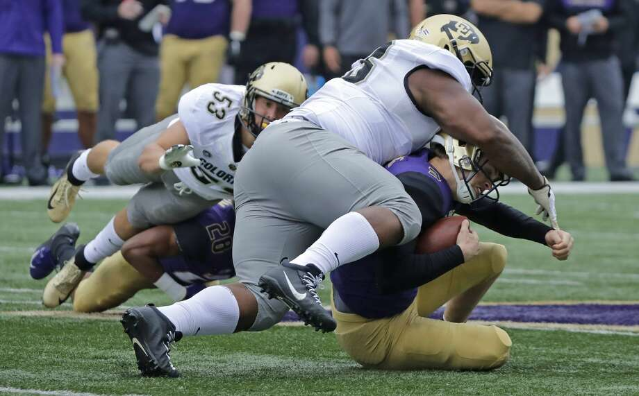Washington quarterback Jake Browning, lower right, is tackled by Colorado's Javier Edwards, upper right, during the first half of an NCAA college football game, Saturday, Oct. 20, 2018, in Seattle. (AP Photo/Ted S. Warren) Photo: Ted S. Warren/AP