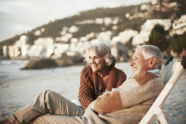 Happy senior couple relaxing on deck chairs at beach