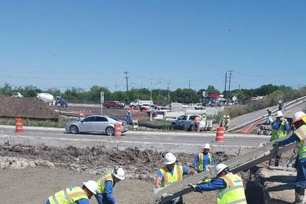 Crews pour asphalt as they complete a sewer line repair on Highway 90 on April 25, 2019.