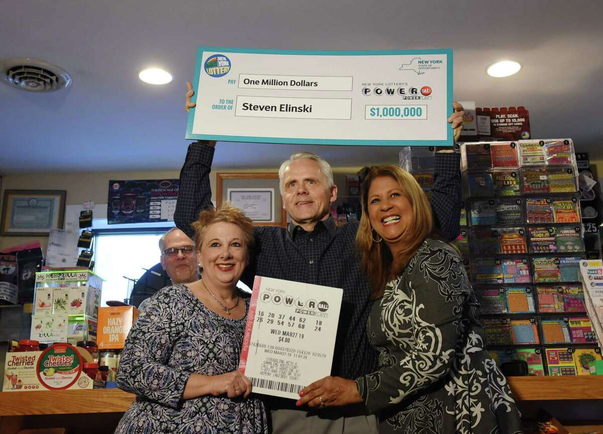 Yolanda Vega awards Steven and Barbara Elinski their $1,000,000 prize during the New York Lottery check presentation, on Friday, April 26, 2019 at LePage Distributing in Cohoes, NY. (Phoebe Sheehan/Times Union)