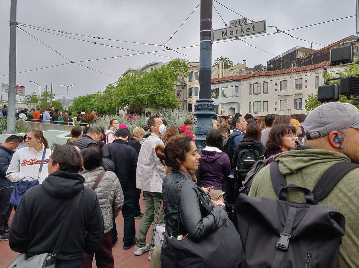 A hordeof commuters wait to board a bus during a nightmarish rush hour Friday morning
