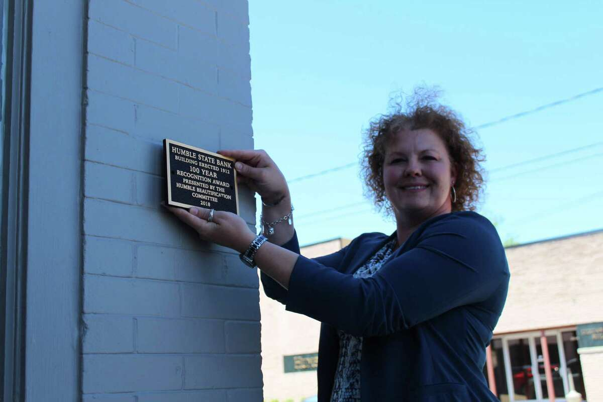 Humble Beautification Committee President Gwen Willis places a plaque on the Humble State Bank located on Main Street on April 25, 2019.