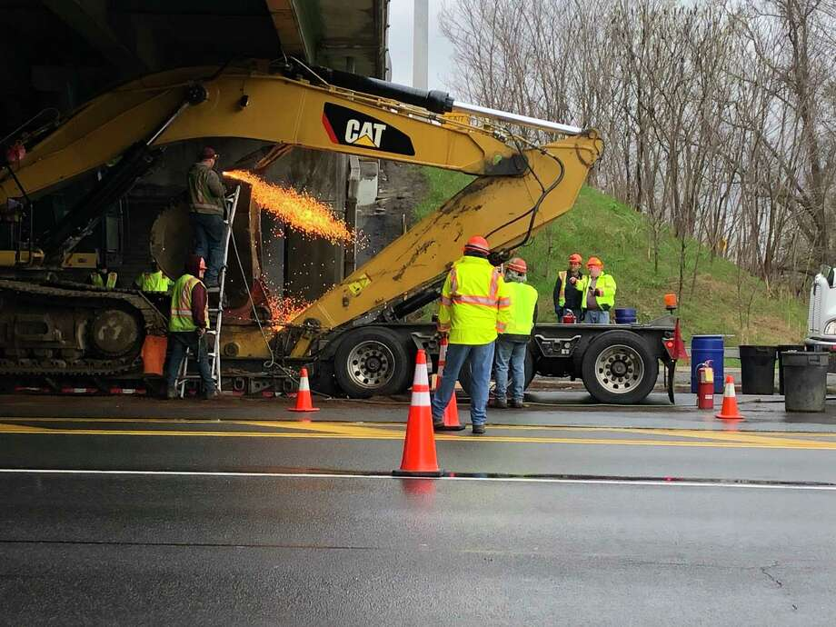 Crews work to remove an excavator wedged under the Northway at the Route 146 bridge in Clifton Park. Photo: Joyce Bassett, Times Union