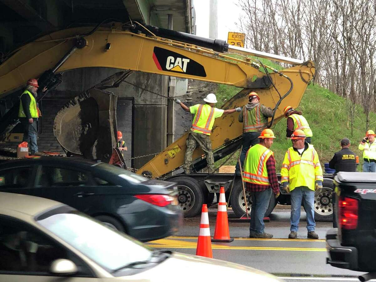 Crews work to remove an excavator wedged under the Northway at the Route 146 bridge in Clifton Park.