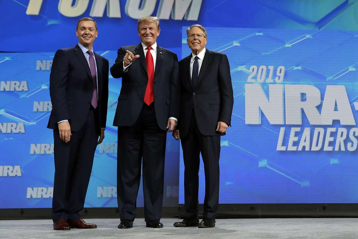 President Donald Trump stands with Chris Cox, Executive Director of the National Rifle Association's Institute for Legislative Action, left and NRA executive vice president and CEO Wayne LaPierre, right, as he arrives to speak to the annual meeting of the National Rifle Association, Friday, April 26, 2019, in Indianapolis. (AP Photo/Evan Vucci)