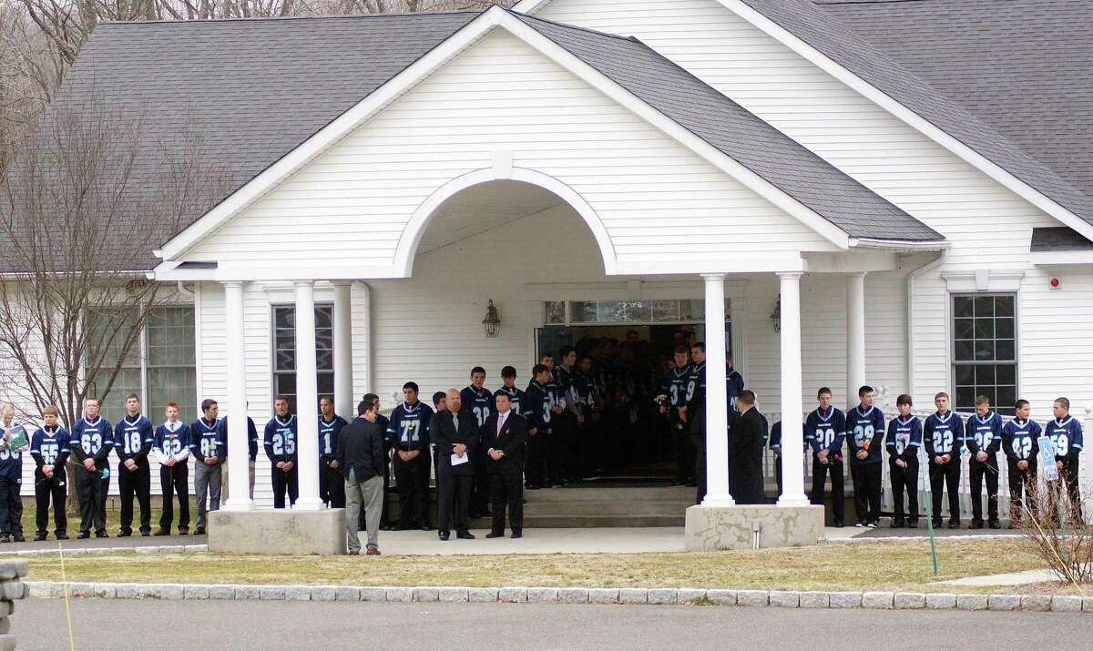 Members of the Oxford High School football team line the driveway outside the Cornerstone Assembly of God Church as they await the casket of their teammate Brandon Giordano before his March 16, 2012 funeral.