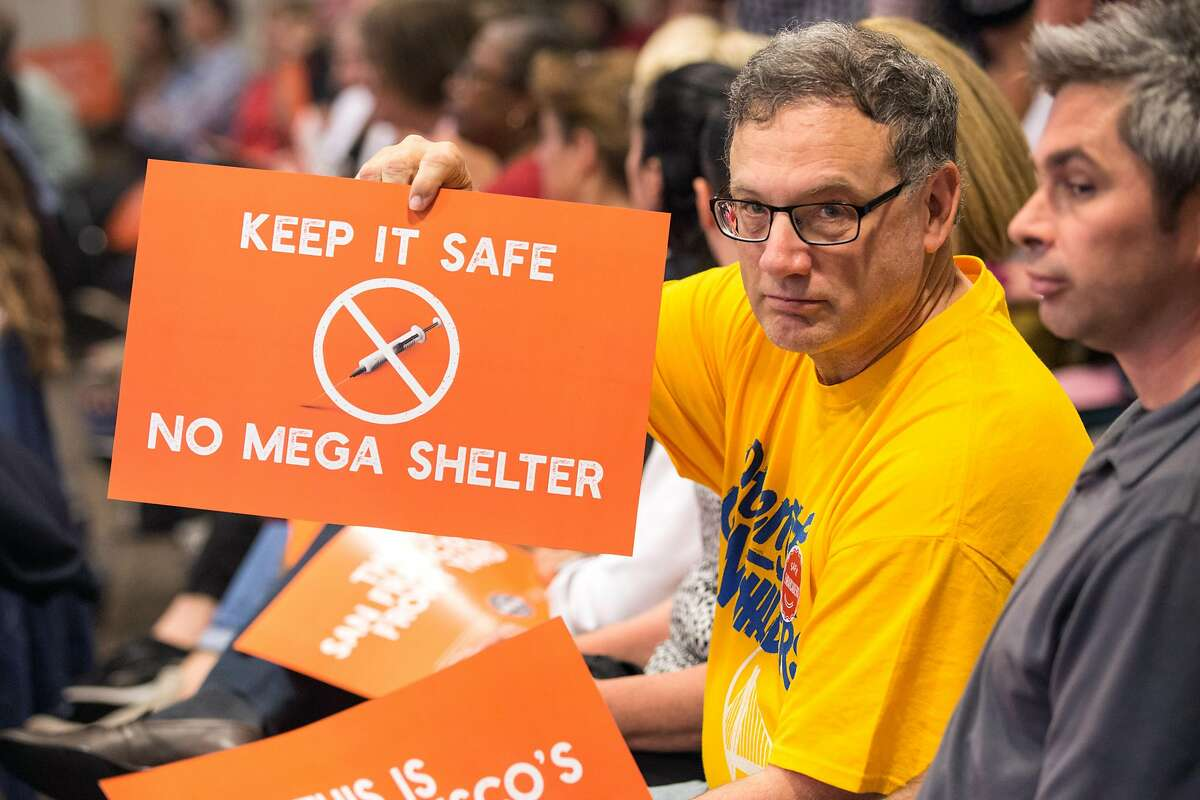 Bruce Guldetsky holds a sign during the Port Commission meeting at Ferry Building that will determine whether a homeless navigation center/shelter will be built on the Embarcadero. Tuesday, April 23, 2019. San Francisco, Calif.