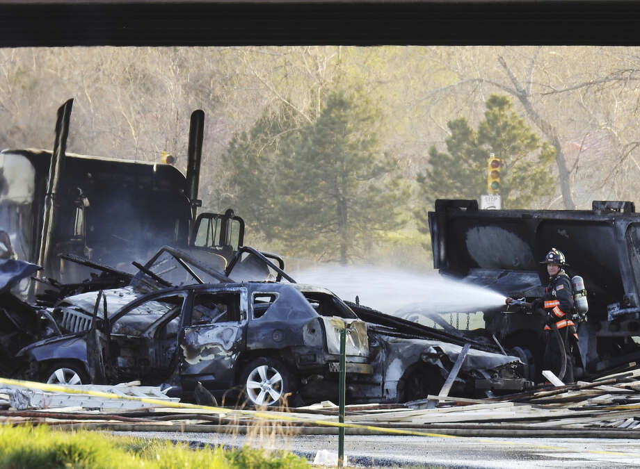 A firefighter sprays water on the wreckage in Lakewood, Colo., Thursday after a deadly collision on Interstate 70 near the Colorado Mills Parkway. On Friday, police said the truck driver blamed for causing the fatal pileup involving over two dozen vehicles has been arrested on vehicular homicide charges. Photo: Hyoung Chang/The Denver Post Via AP