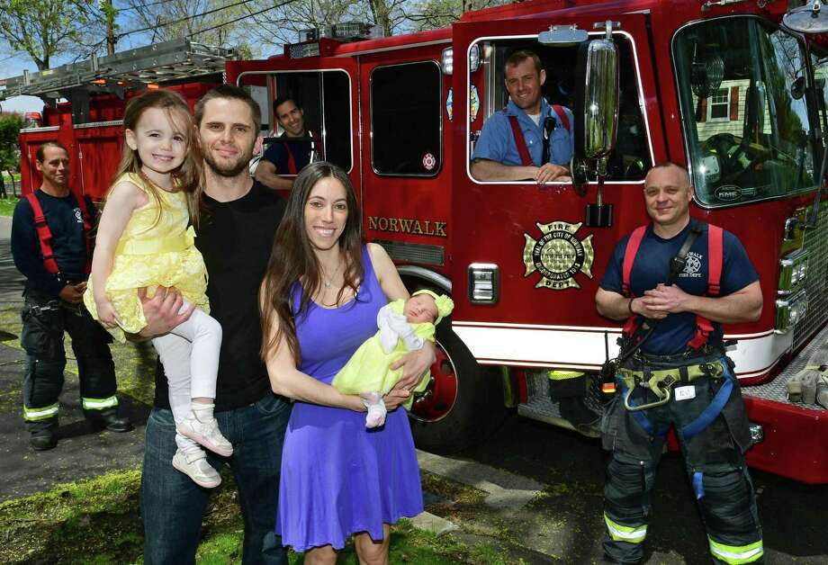 Norwalk firefighter David Dustin and his wife Christina and their daughter Grace, 3, and newborn, Allie, at their home Thursday, April 25, 2019, in Norwalk, Conn. Last Friday Norwalk firefighters and paramedics assisted in the birth of the Dustin's new daughter after Christina had to give birth in the ambulance on the way to the hospital. Photo: Erik Trautmann / Hearst Connecticut Media / Norwalk Hour