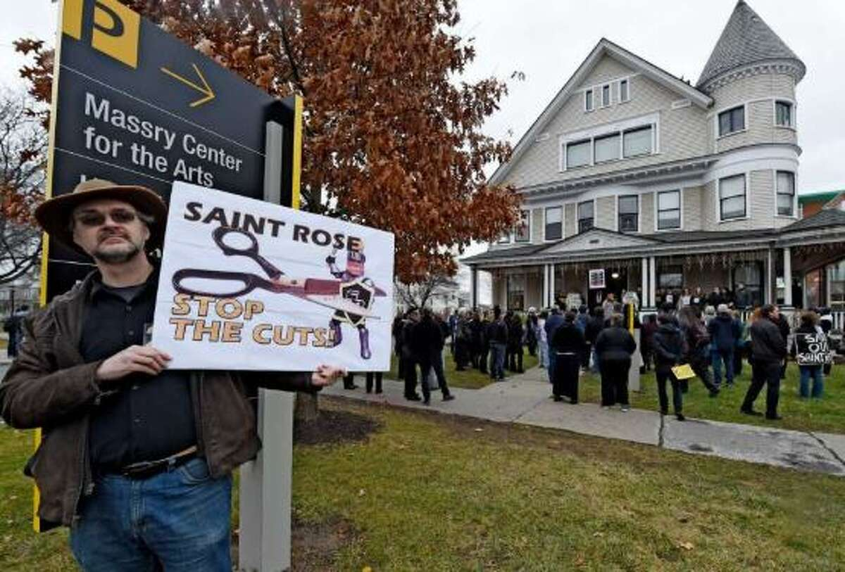 Bradley Russell, adjunct professor of anthropology and sociology holds a sign to the street as Saint Rose students, faculty and staff hold a mock funeral in response to faculty layoffs and program cuts at Saint Rose College Tuesday afternoon Dec. 15, 2015 in front of the Administration building in Albany, N.Y.