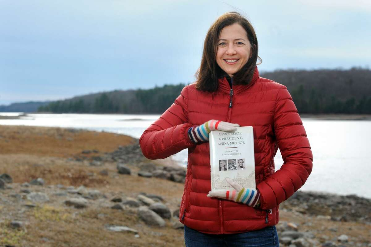 """Cathryn J. Prince stands with a copy of her book """"A Professor, a President and a Meteor"""" near Easton Reservoir in Trumbull, Conn. Dec. 6, 2017."""