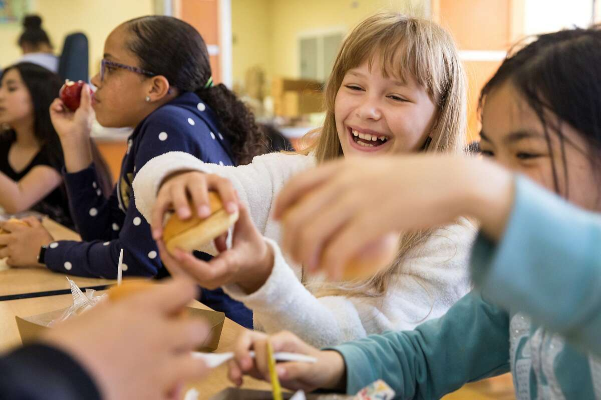 Eva Savchik, center, with Angela Hoang, right, 5th graders, sit down together for lunch at the Tenderloin Community School on Thursday, April 25, 2019. San Francisco, Calif.