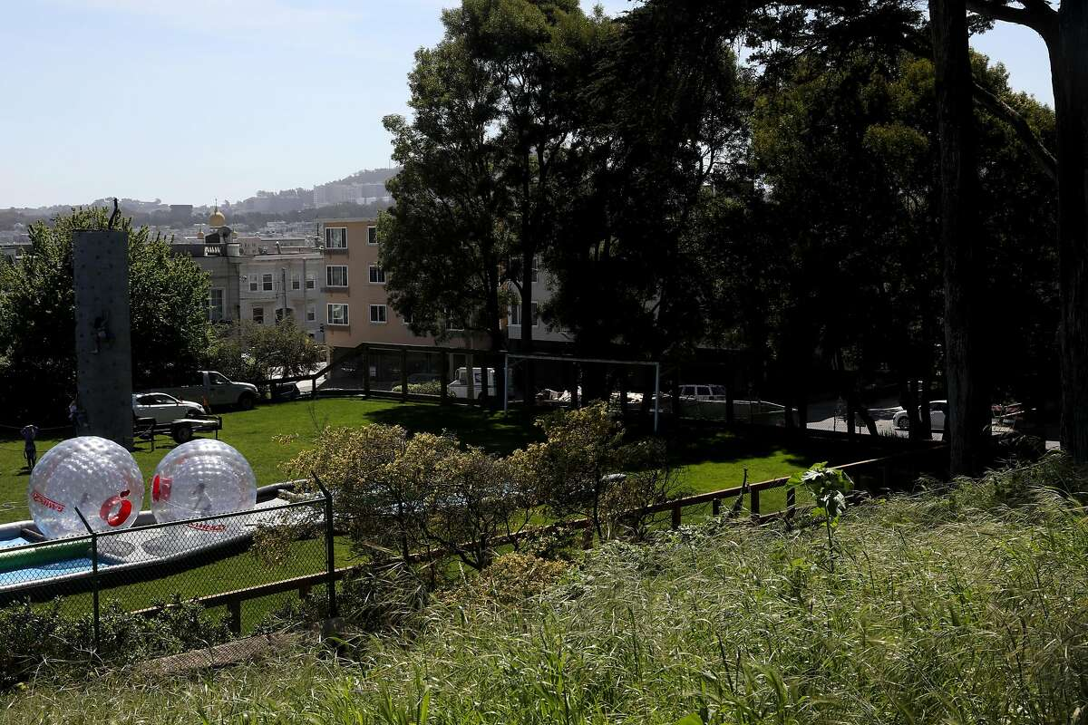 View of playground at the Katherine Delmar Burke School (left) with the building of Igor Perlov beyond wall of trees across the street at right on Friday, April 12, 2019, in San Francisco, Calif. Igor Perlov called the FBI four times last year saying voices in his head were telling him to commit a mass shooting.