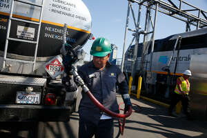 FILE PHOTO : Memo Terrones, Golden Gate Petroleum driver, returns a nozzle to the fuel truck after a Capital Corridor locomotive is filled with renewable diesel at the Amtrak Maintenance Facility on Tuesday, September 12, 2017 in Oakland, Calif. Tightening carbon standards in California are expected to boost demand for renewable diesel and other low carbon fuels. San Antonio's Valero Energy is upgraded its renewable diesel facility New Orleans it owns through a subsidiary called Diamond Alternative Energy.