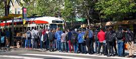 People stand at a bus stop at Market and Church Street waiting for shuttle buses headed downtown. After a power line failure commuters had to take alternative route to get to their destinations.  on Friday, April 26, 2019. San Francisco, Calif.