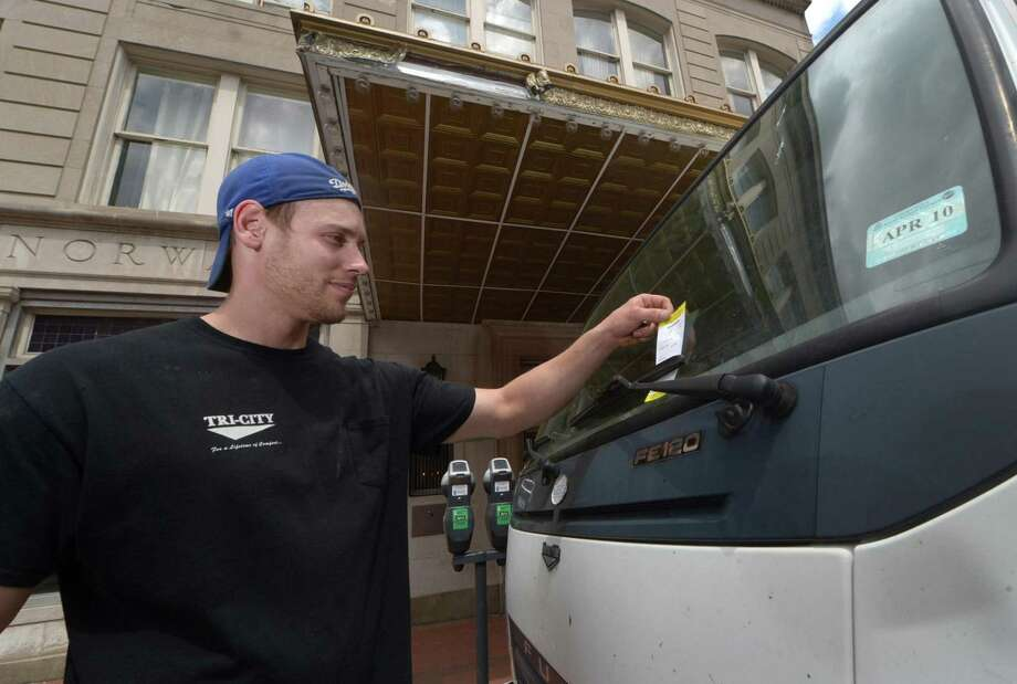 Tri-City Appliance employee Justin Frey looks at a parking ticket on the windshield of his work truck parked on Washington Street Tuesday, May 2, 2017, in South Norwalk, Conn, during the highest year of ticketing for the Authority. The Authority reports that since then, a change in practices has reduced the number of tickets given out. Photo: Erik Trautmann / Hearst Connecticut Media / Norwalk Hour