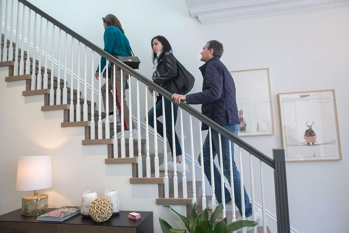 """Maria Borda, left, Maria Gutman, center and Jeff Silver walk up the stairs during their visit of a house that was featured on the 1980 t.v. show """"Full House"""" and which is officially hitting the market next week. On Friday, April 26, 2019. San Francisco, Calif."""