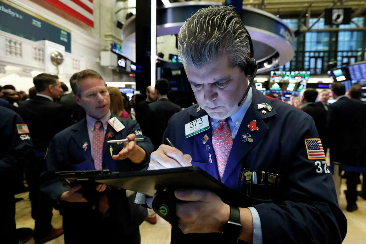 FILE - In this March 11, 2019, file photo trader John Panin, right, works on the floor of the New York Stock Exchange. The U.S. stock market opens at 9:30 a.m. EDT on Friday, April 26. (AP Photo/Richard Drew, File)