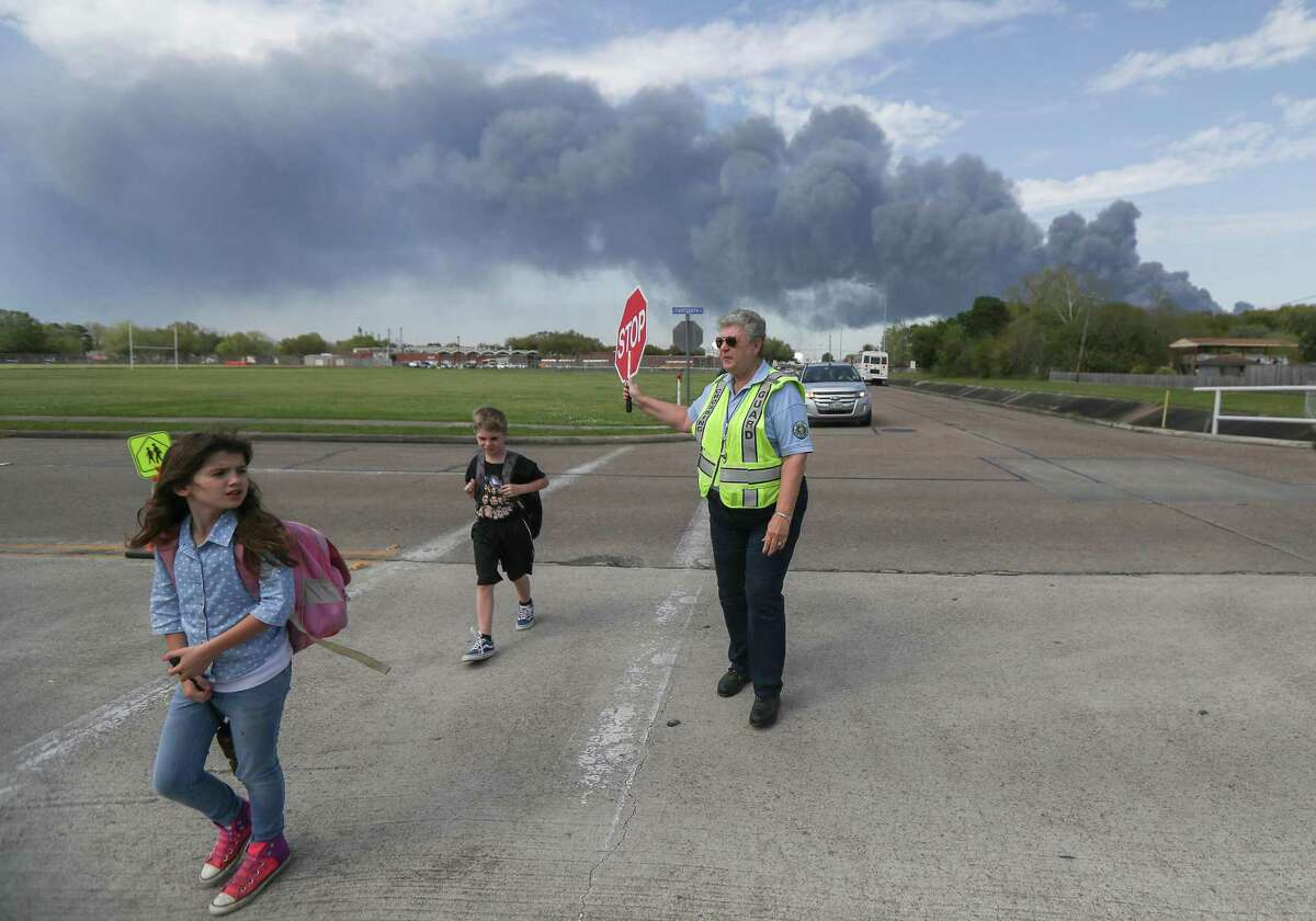 Deer Park PD Crossing Guard Adell Boren makes sure students are safe as they cross East 13th and Meadowlark Streets in spite of a chemical fire burning nearby Tuesday, March 19, 2019, in Deer Park.