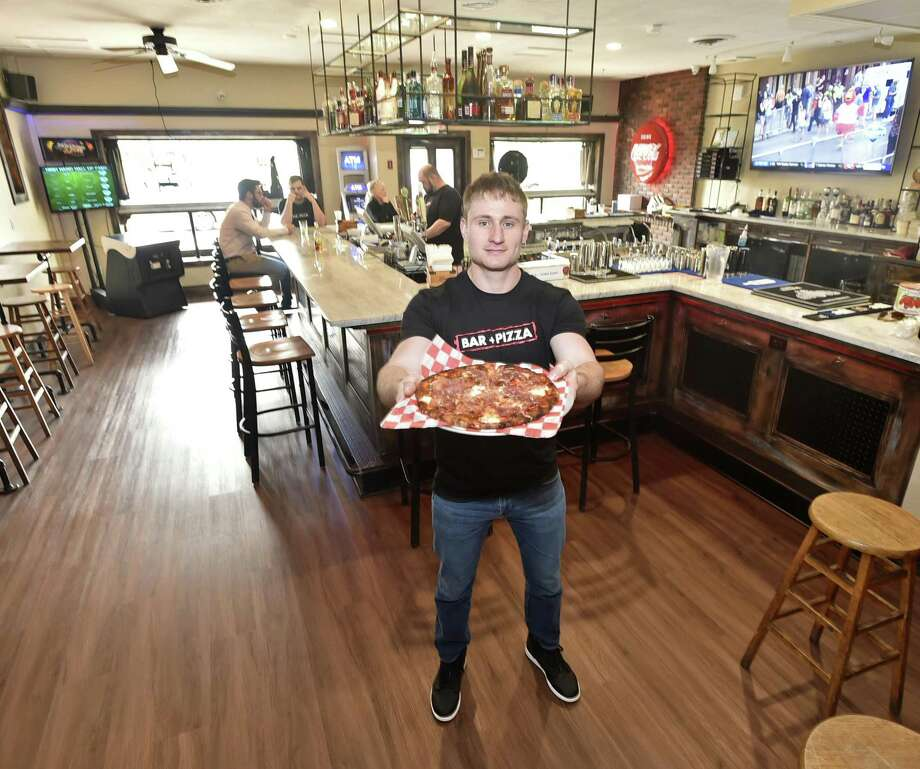 Steve Morrell, owner of Rebar, a pizza restaurant and bar in West Haven, holds his signature THE REBAR: A pizza of mozzarella, prosciutto, burrata, pepperoni, hot cherry peppers, red onion and truffle honey. Photo: Peter Hvizdak / Hearst Connecticut Media / New Haven Register