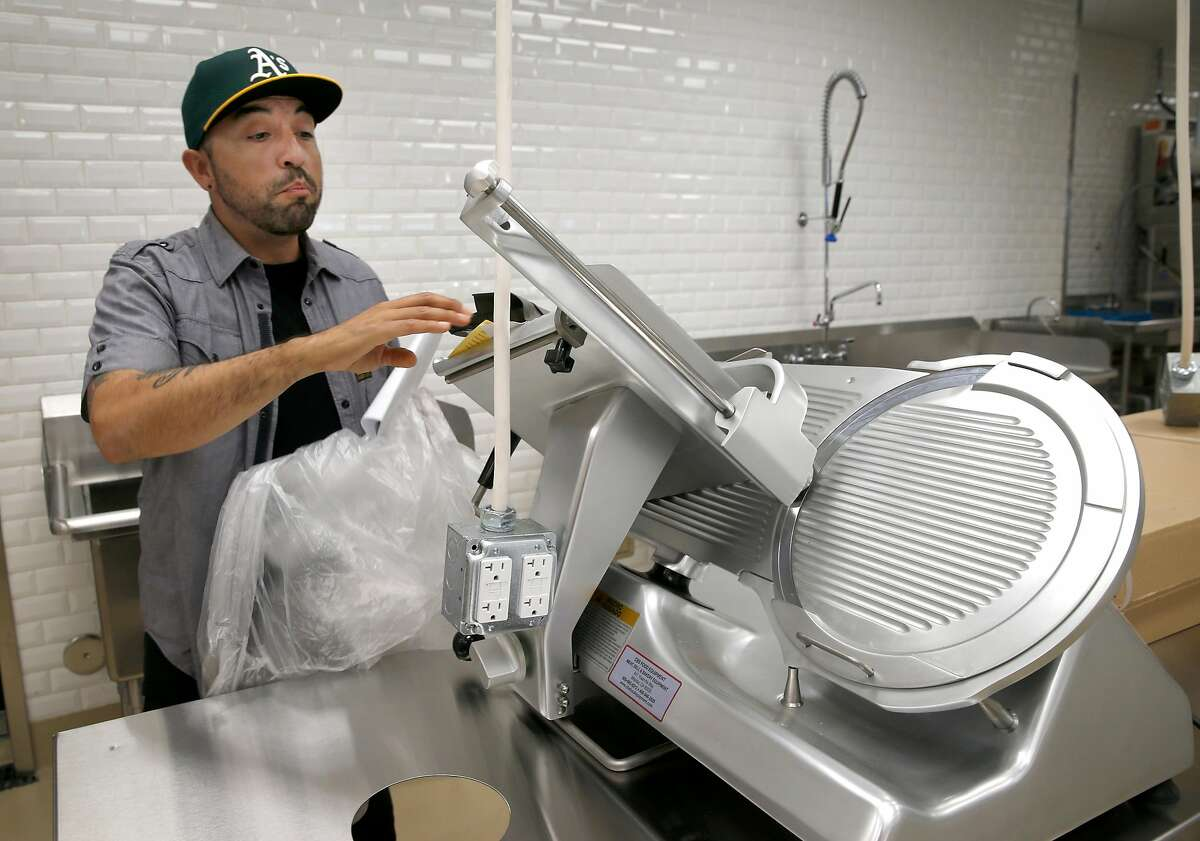 Food service manager Fausto Howay unwraps a new meat slicer at the new Community Foods Market on San Pablo Avenue in Oakland, Calif. on Friday, April 26, 2019. The new grocery store, which will also serve as a gathering space for the community, will be the first full service market to open in a West Oakland neighborhood long considered to be a food desert.