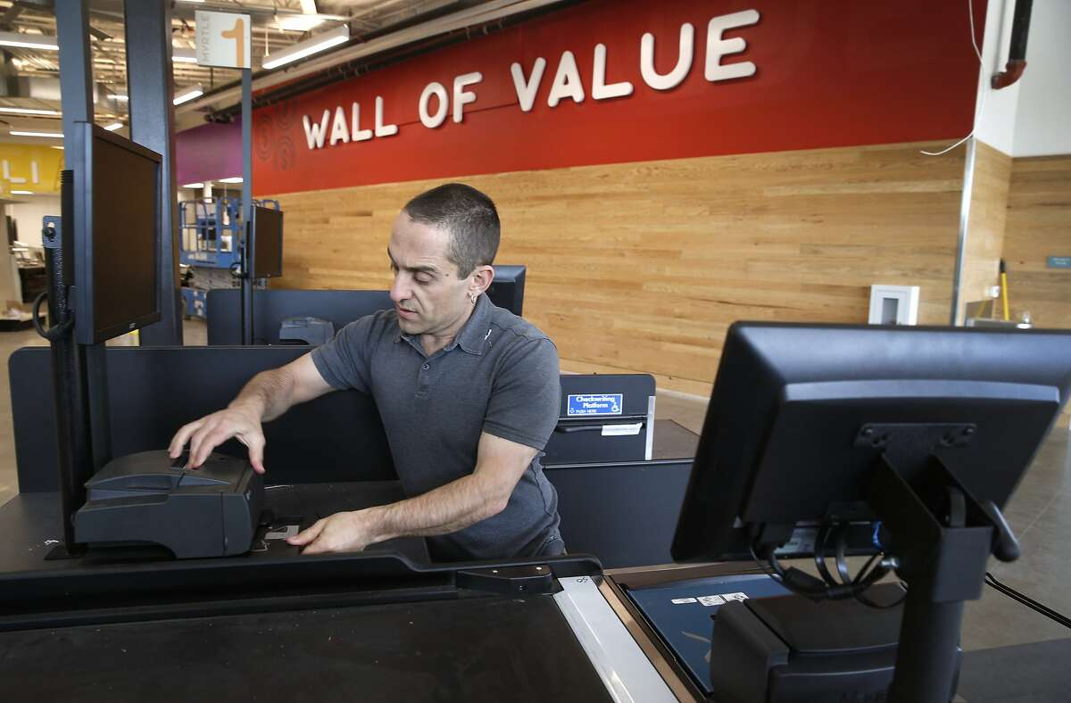 Brahm Ahmadi, CEO and co-founder of the Community Foods Market, arranges one of the checkout stands inside the store on San Pablo Avenue, in Oakland, Calif. on Friday, April 26, 2019. The new grocery store, which will also serve as a gathering space for the community, will be the first full service market to open in a West Oakland neighborhood long considered to be a food desert.