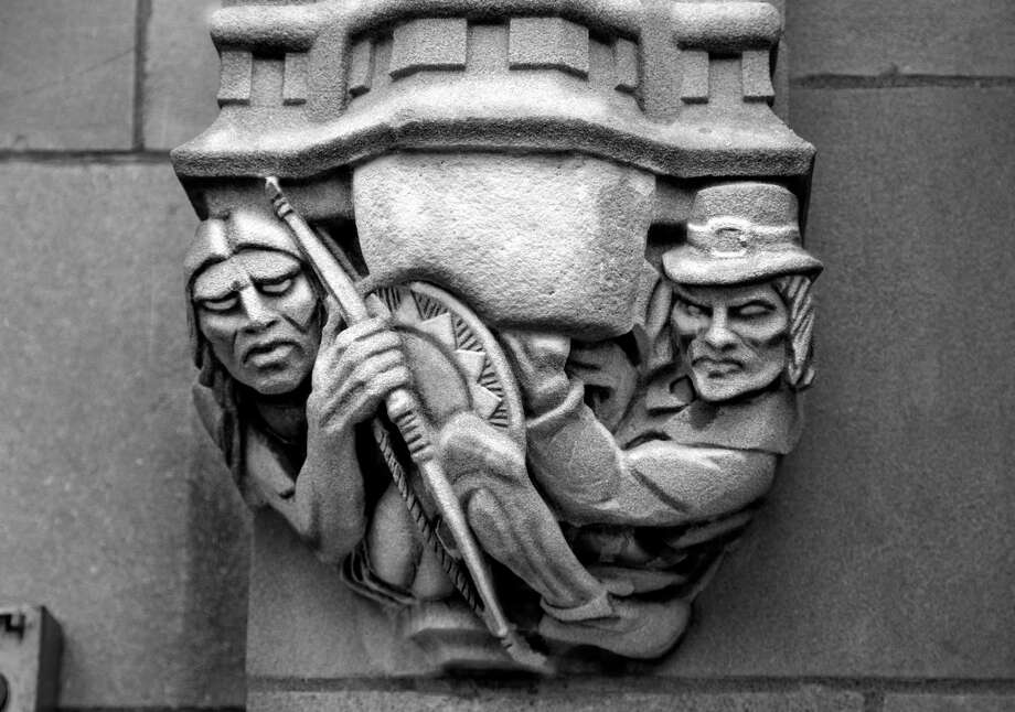 The original stone carving on the back of Sterling Memorial Library showing a Puritan aiming a musket at a Native American (left photo) was altered by order of Yale officials, covering up the gun (right photo). Later the entire carving was removed. Photo: Contributed / Mathew Duman / Copyright 2017 Mathew M. Duman