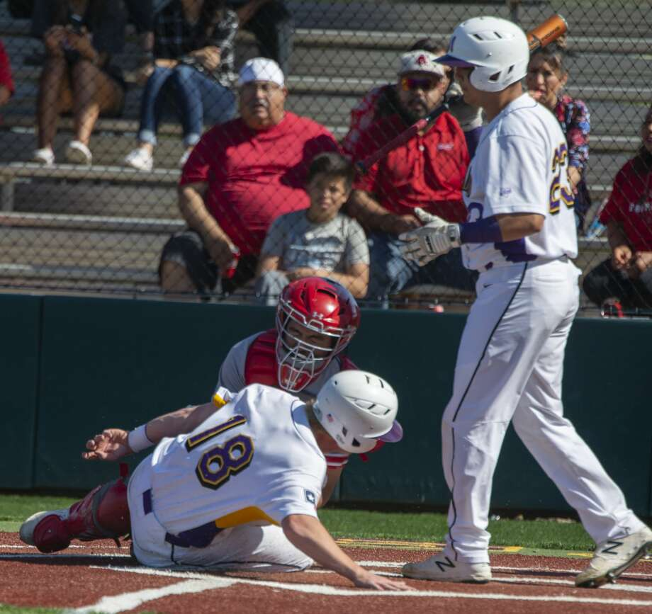 Midland High's Sean Porter safely slides into home on a steal as Ryan Grantham bats 04/26/19 as Odessa High's catcher, Pilar Ramirez, is late with the tag. Tim Fischer/Reporter-Telegram Photo: Tim Fischer/Midland Reporter-Telegram