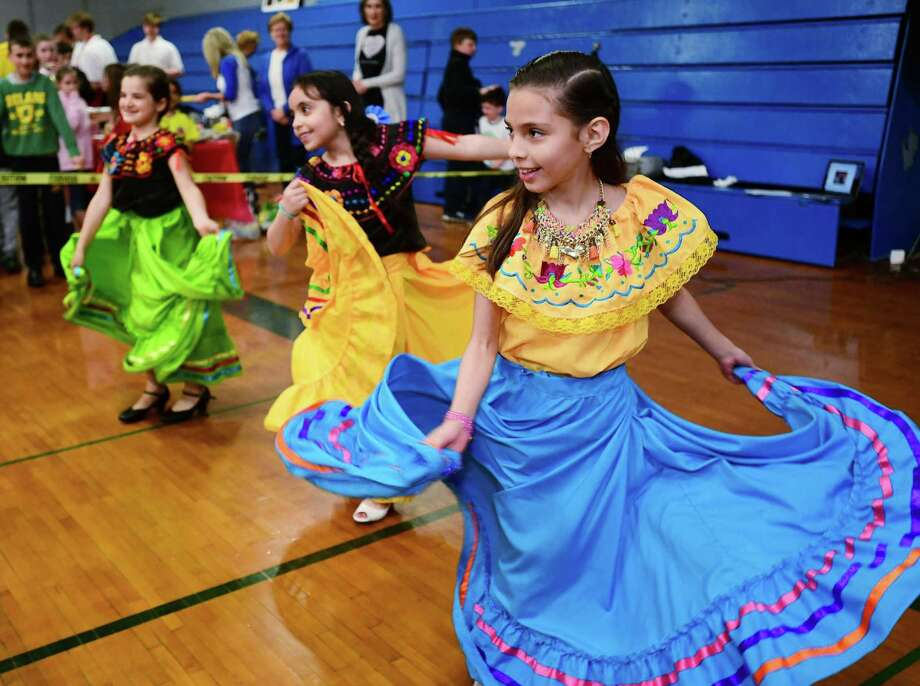 Second graders Leticia Dearrese, Alexa Orozco and Samantha Miranda perform a trdaitional Mexican dance as students and their families attend All Saints Catholic School's annual international night Friday, April 26, 2019, showcasing the cultural diversity of the school in Norwalk, Conn. The food, dances and presentations represented more than 30 countries. Photo: Erik Trautmann / Hearst Connecticut Media / Norwalk Hour