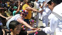 People at the 2019 Battle of Flowers Parade along Broadway greet members of the U.S. Navy. Mayor Ron Nirenberg issued a statement Friday that offered a wait-and-see stance on Fiesta, this city's biggest annual cultural event.