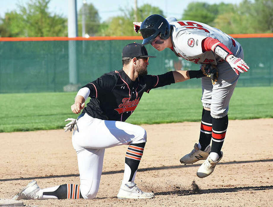 Edwardsville third baseman Max Ringering, left, tags out Alton's Adam Stilts in the third inning after his two-run double Friday at Tom Pile Field in Edwardsville. Photo: Matt Kamp | For The Telegraph