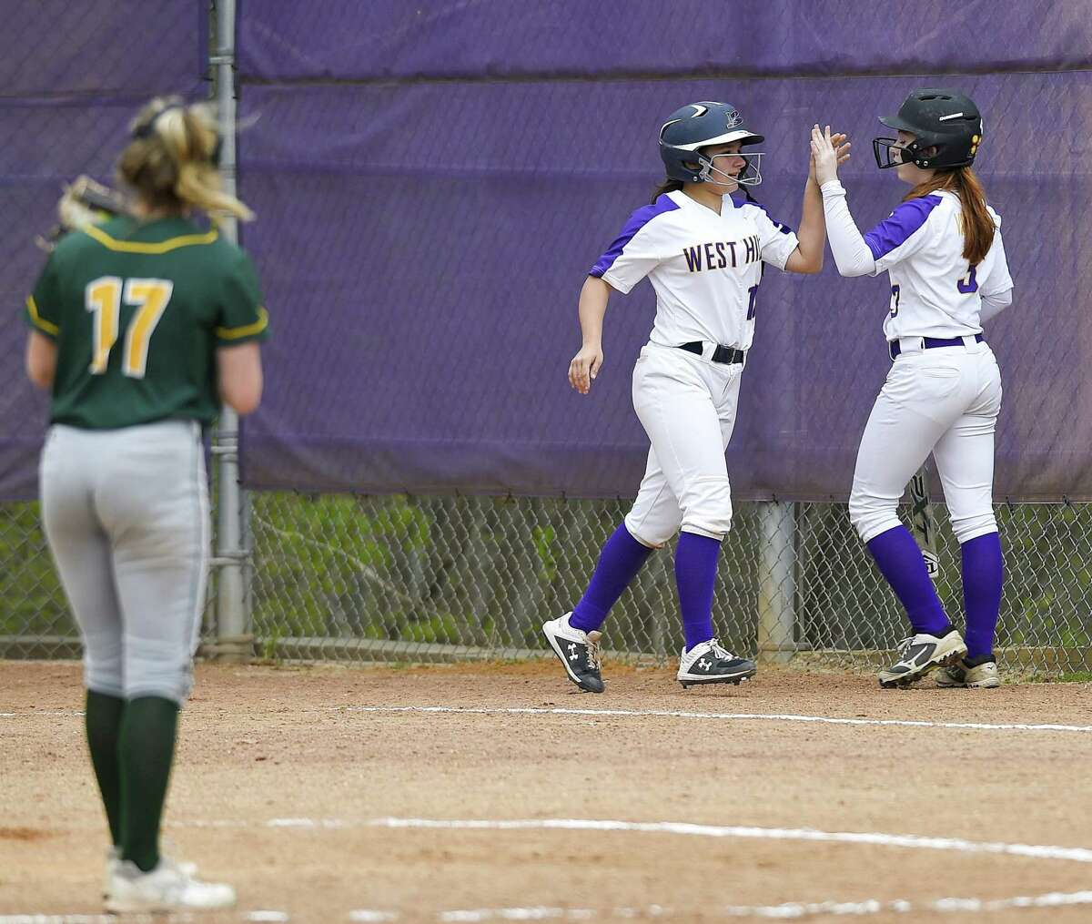 Westhill's Kirsten Hallinan high fives Kara Sciglimpaglia after scoring on an RBI double against Trinity Catholic in the third inning on Thursday.