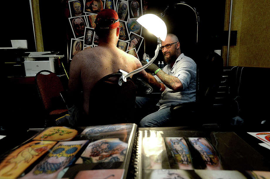 Bridge City-based tattoo artist Flipper gives a first tattoo to Mike Lund during the Beaumont, Texas Tattoo Expo, sponsored by Ink Masters Tattoo Show Friday at the MCM Elegante Hotel. The expo continues through the weekend - Saturday 11 a.m. - 11 p.m. and Sunday 11 a.m - 9 p.m. Over one hundred artists and other vendors offered tattoos and piercing on site, in addition to showcasing their skills, new trends in tattooing and related products.   Photo taken Friday, April 26, 2019 Kim Brent/The Enterprise Photo: Kim Brent/The Enterprise