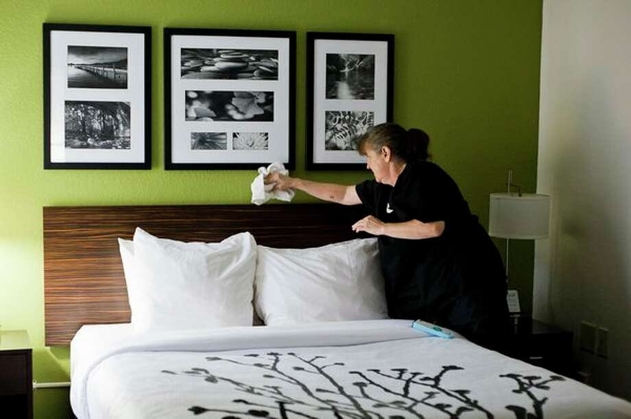 Housekeeper Tammi Long of Midland wipes down framed photos above a bed during her shift at the Sleep Inn on Friday morning in Midland. 'I do make my bed like this at home,' Long said. 'Then my husband messes it up and I get mad at him,' she added. (Katy Kildee/kkildee@mdn.net)