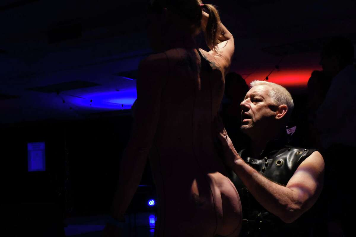 Andy Cargile paints Tanna Foss on opening night of the annual Seattle Erotic Arts Festival, April 26, 2019.