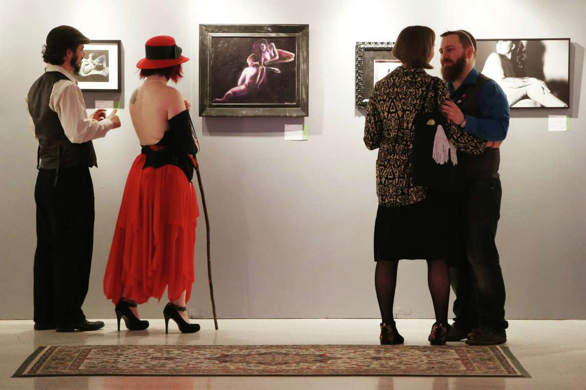 People browse through the artwork on opening night of the annual Seattle Erotic Arts Festival, April 26, 2019.