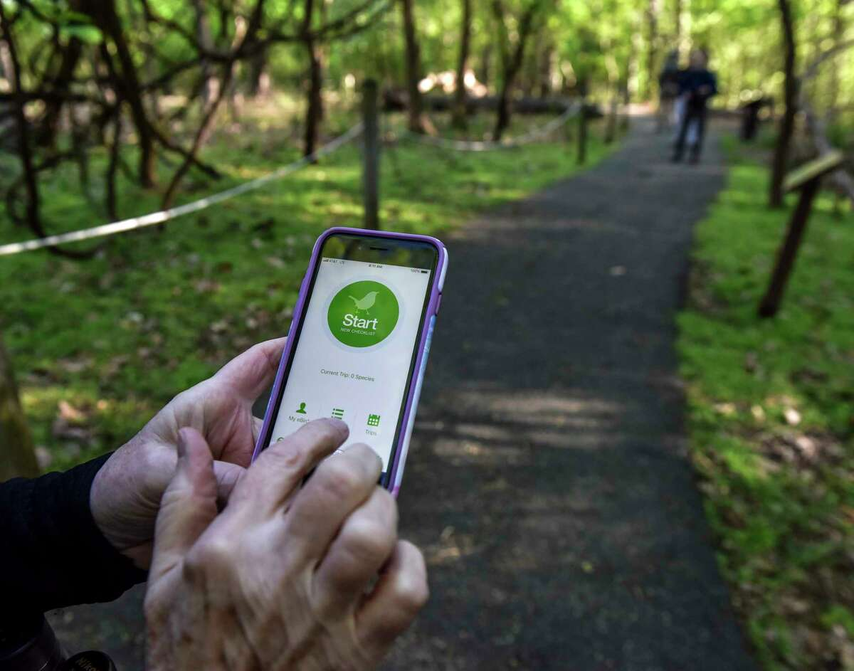 A birdwatcher launches the eBird app to record her sightings at the District of Columbia's Rock Creek Park. With the app, Cornell Lab collects millions of sightings.