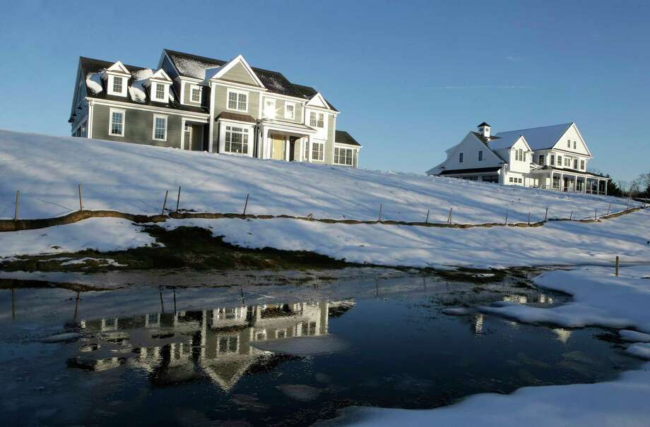 FILE- In this Feb. 21, 2019, file photo a recently constructed home, left, is reflected in water, in Natick, Mass. Before squeezing every last nickel into a down payment on a home mortgage, set some cash aside to handle unexpected expenses after the closing. (AP Photo/Steven Senne, File) Photo: Steven Senne / Copyright 2019 The Associated Press. All rights reserved