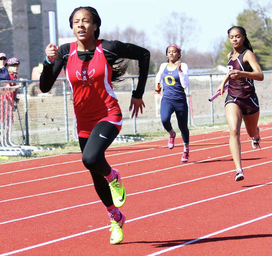 Alton's Renee Raglin (left) runs the second leg of the Redbirds' 4x200 relay during the Southwestern Illinois Relays on March 22 in Edwardsville. The Redbirds on Friday finished second in the Collinsville Invite. Photo: Greg Shashack / The Telegraph
