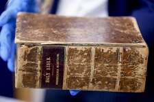 FBI supervisory special agent Shawn Brokos, right, shows the theft recovered 1615 Breeches Edition Bible during a news conference, Thursday, April 25, 2019, in Pittsburgh. The Bible was stolen from the Carnegie Library in Pittsburgh in the 1990's. It was traced to the American Pilgrim Museum in Leiden, Netherlands. (AP Photo/Keith Srakocic)