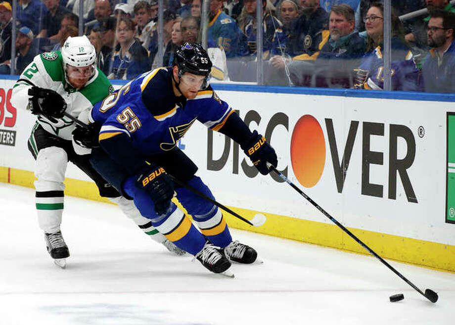 The Blues' Colton Parayko (right) gets to a loose puck in front of the Stars' Radek Faksa in Game 2 on Saturday in St. Louis. Photo: Associated Press