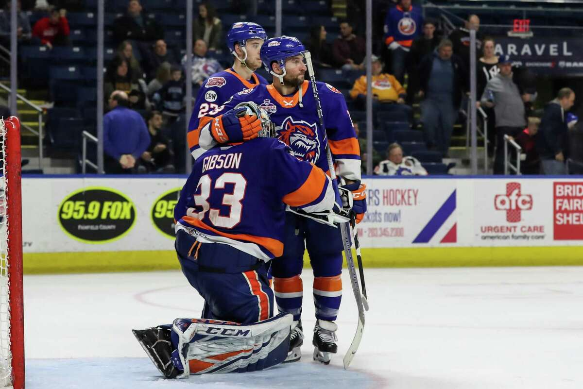 Stephen Gionta (13) of the Bridgeport Sound Tigers consoles goaltender Christopher Gibson (33) after the game five loss that resulted in their elimination from the AHL Calder Cup Playoffs between the Bridgeport Sound Tigers and the Hershey Bears on April 27, 2019 at the Webster Bank Arena in Bridgeport, CT.
