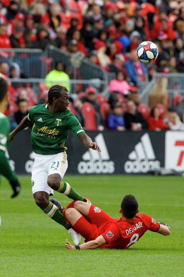 Portland Timbers midfielder Diego Chara (21) keeps an eye on the ball as Toronto FC midfielder Marky Delgado (8) tackles it away during second half MLS soccer action at BMO field in Toronto, Saturday, April 27, 2019. (Cole Burston/The Canadian Press via AP) Photo: Cole Burston / The Canadian Press