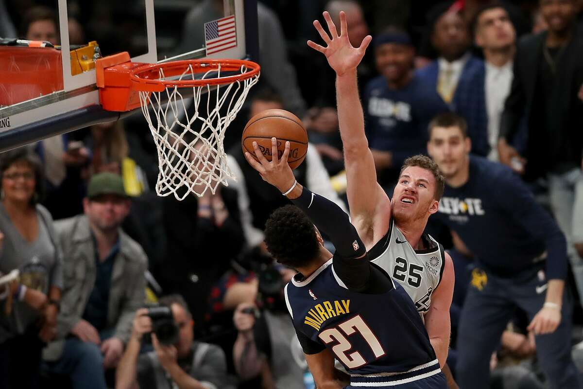 DENVER, COLORADO - APRIL 27: Jamal Murray #27 of the Denver Nuggets is fouled going to the basket by Jakob Poeltl #25 of the San Antonio Spurs in the first quarter during Game Seven of the first round of the 2019 NBA Western Conference Playoffs at the Pepsi Center on April 27, 2019 in Denver.