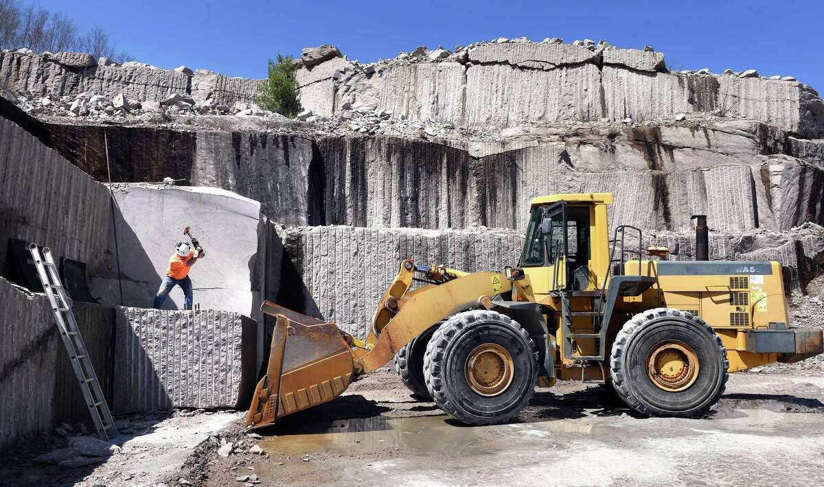 Quarry supervisor Rick Atkinson uses a sledge hammer to drive a steel wedge into granite to split a block at the Stony Creek Quarry in Branford on April 23.