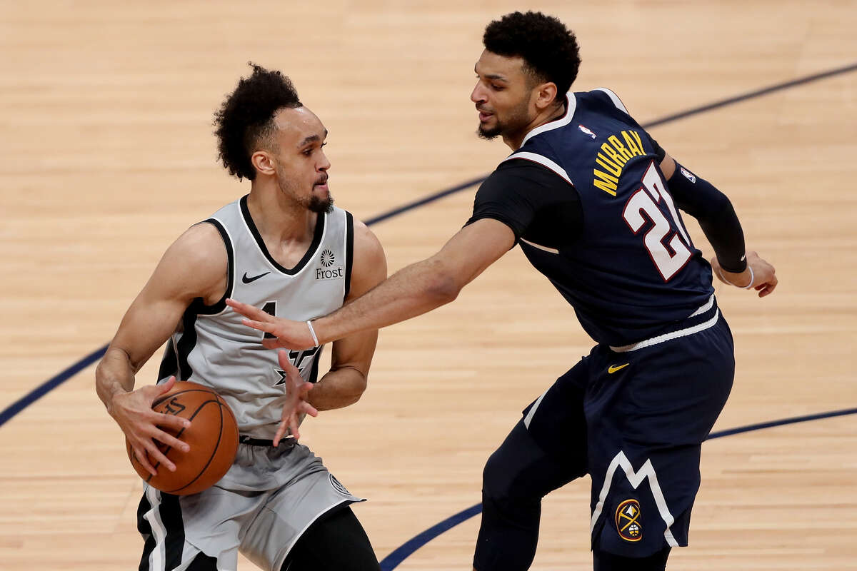 Derrick White #4 of the San Antonio Spurs is fouled by Jamal Murray #27 of the Denver Nuggets in the second quarter during Game Seven of the first round of the 2019 NBA Western Conference Playoffs at the Pepsi Center on April 27, 2019 in Denver.